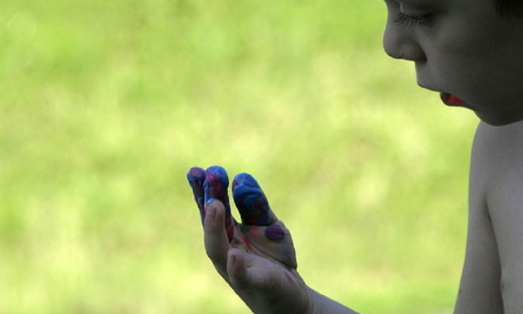 boy looking at red and blue paint on his fingers